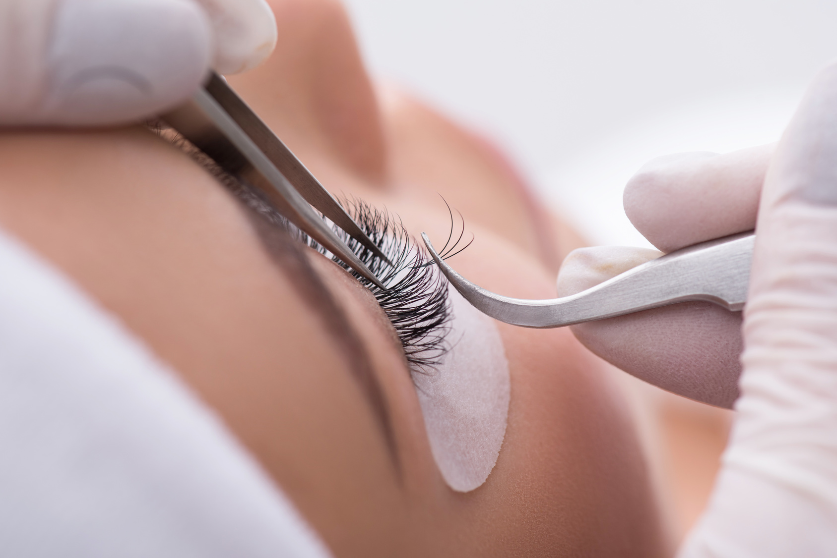 Skillful cosmetologist undergoing lash extension procedure