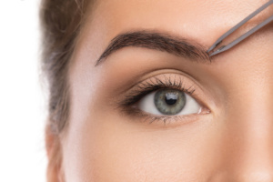 Woman tweeze eyebrows
